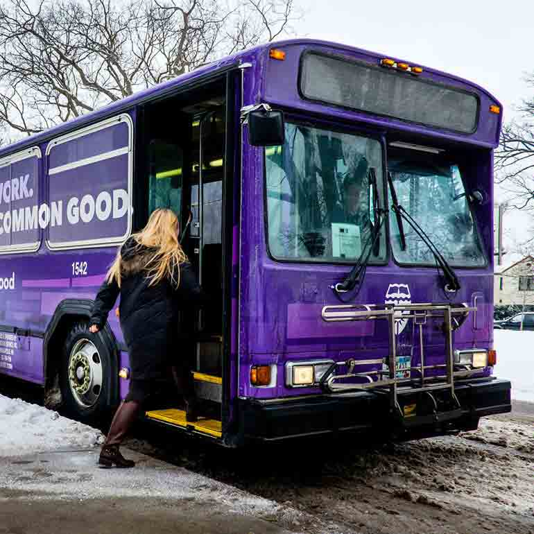 A student boards the St. Thomas shuttle bus.
