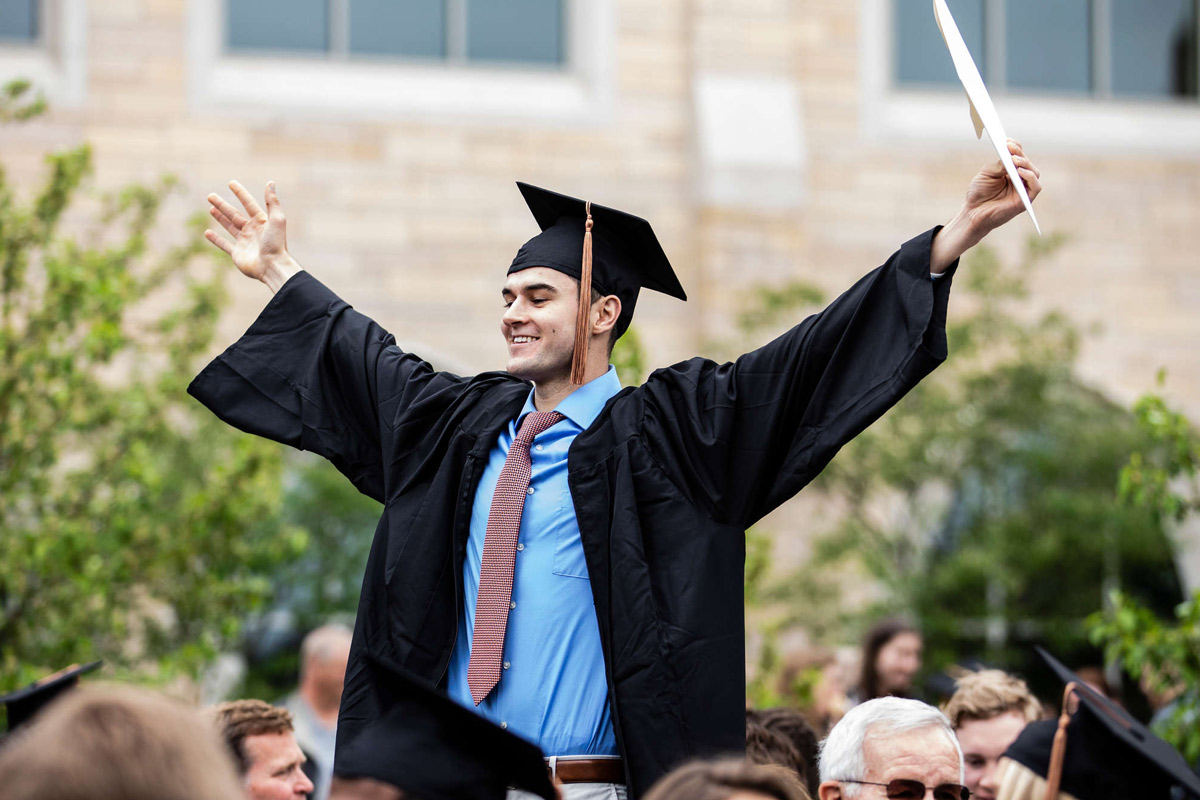Male graduate stands above crowd holding diploma with arms outstretched.
