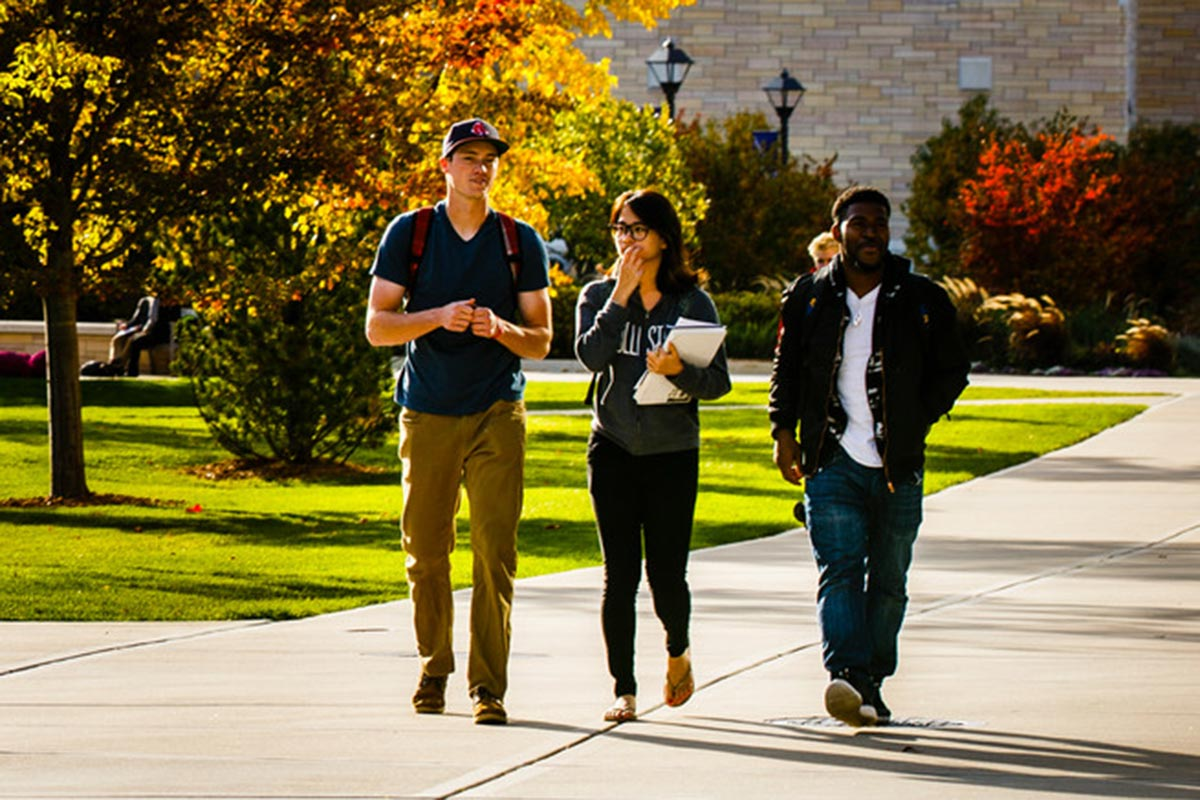 Students walk on campus with autumn foliage in the background.