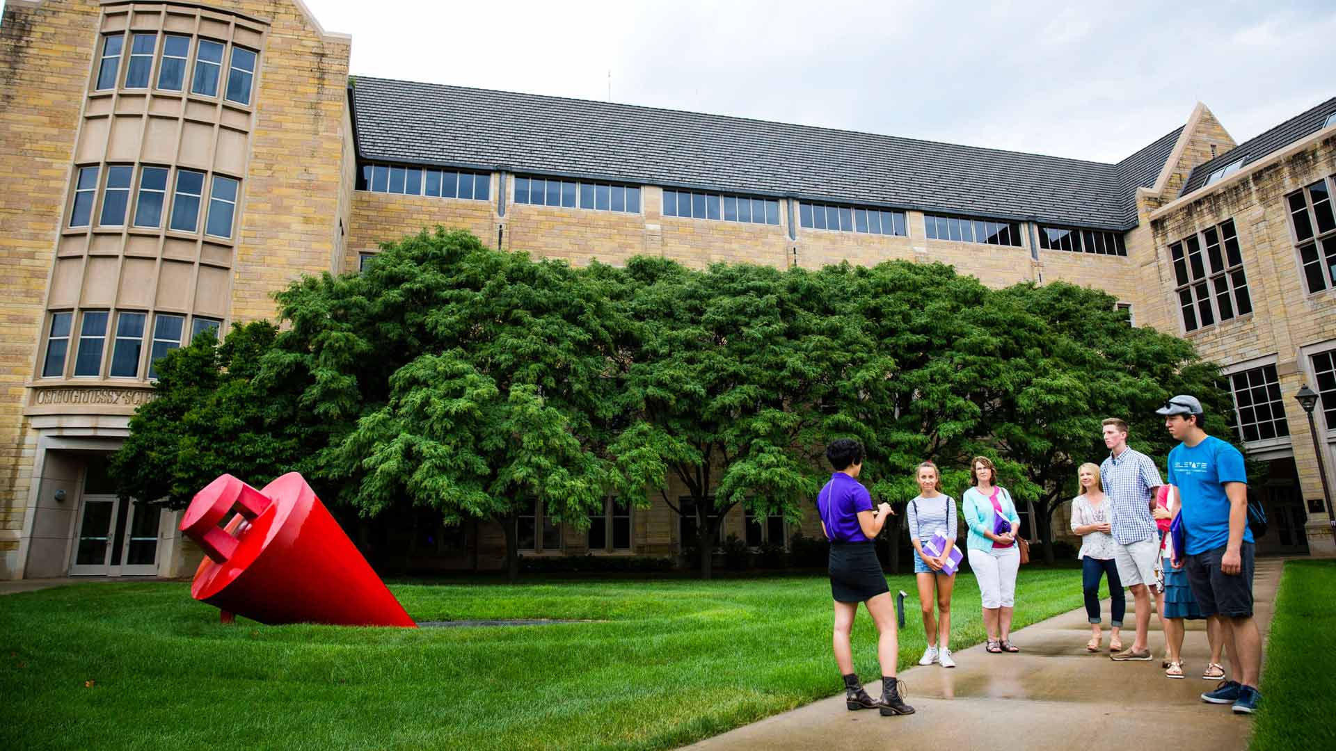 Tour guide and group of high school students and their parents talk near a red sculpture.