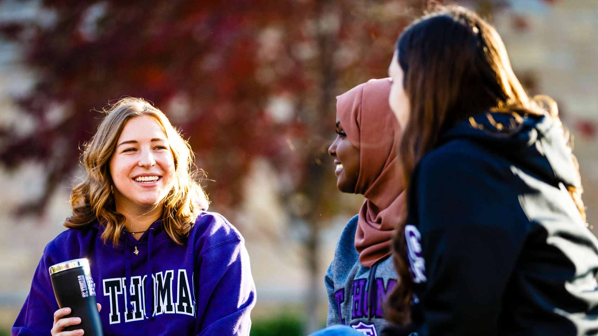 Maddy Rudkin, Najma Mohamed and Erin Engstran sitting and talking on the campus quad.