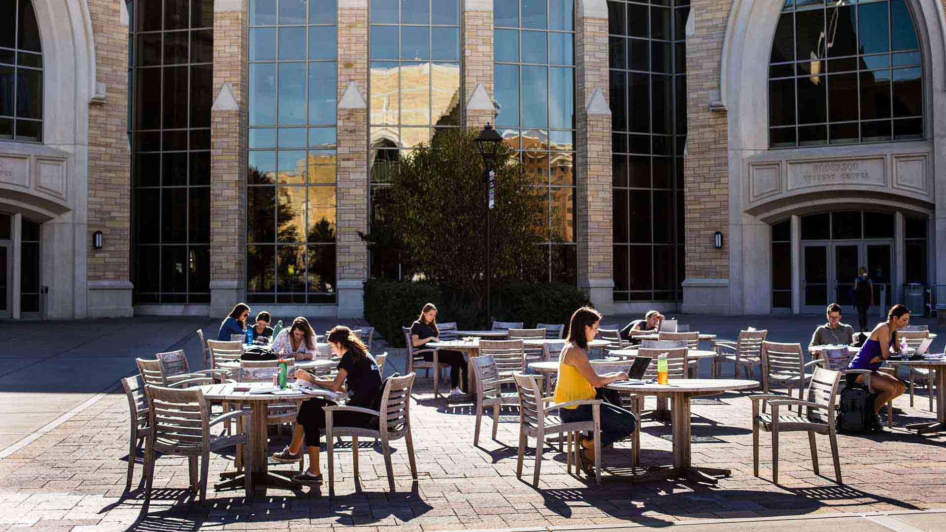 Students study at tables outside of Anderson Hall in the autumn.