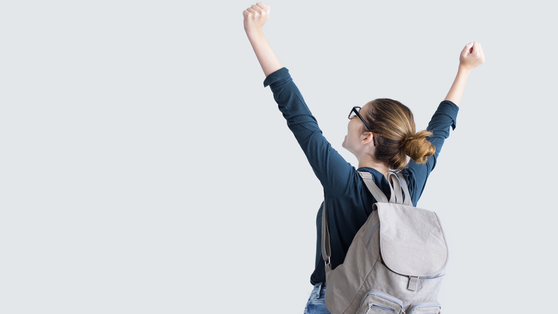 Female student wearing backpack facing away with arms raised.