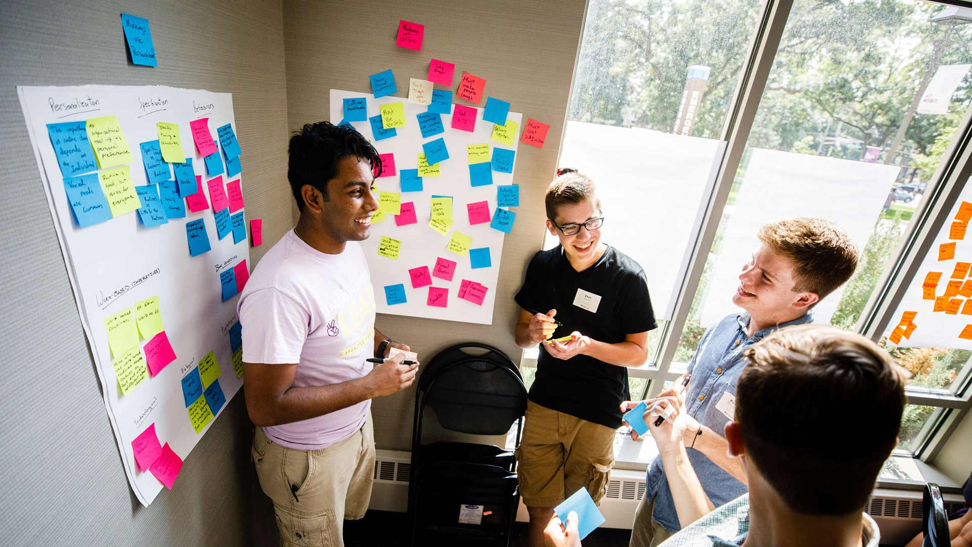Four students brainstorm on post-it notes.