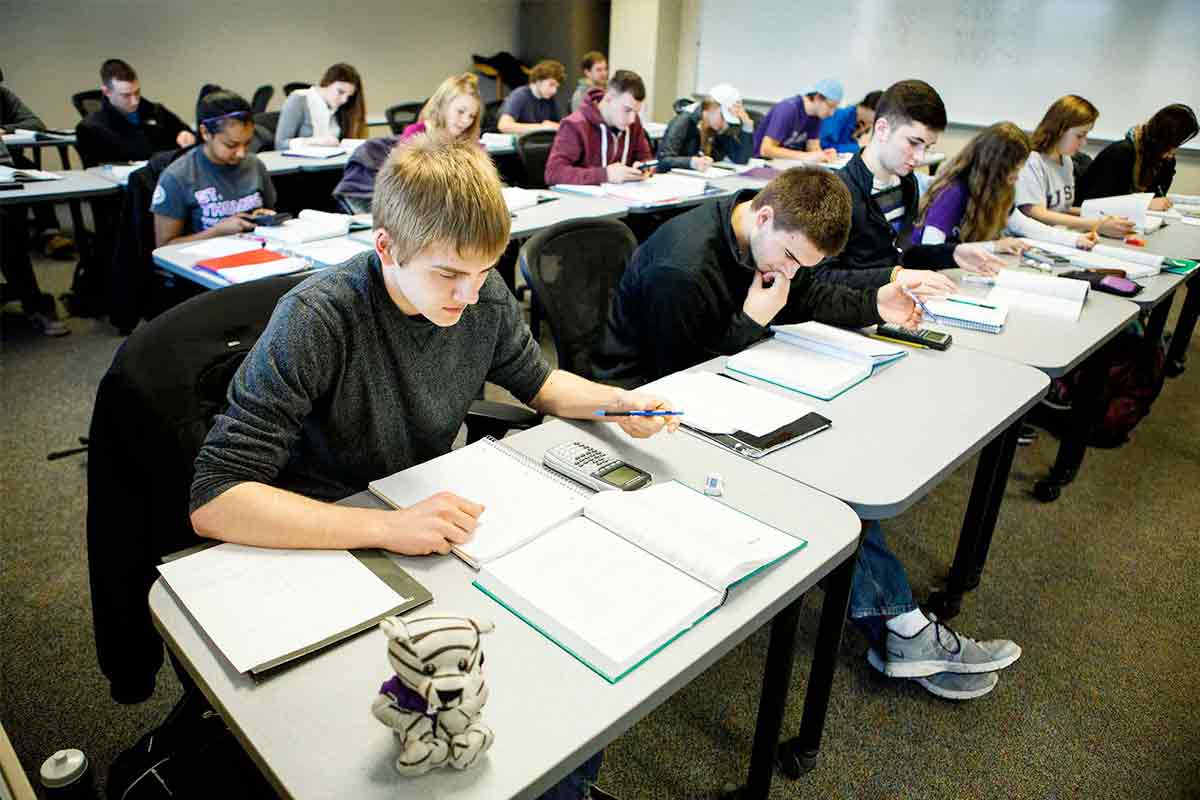 Students work with open textbooks during Actuarial Science class.