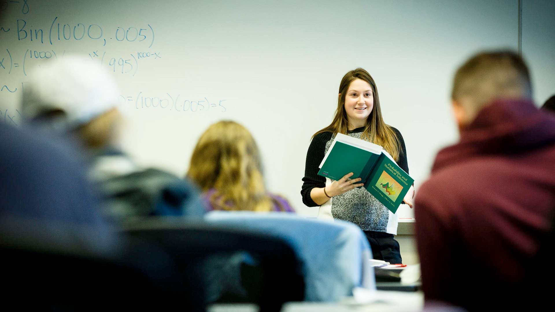 A student holds a textbook while presenting to the class during an actuarial science class.