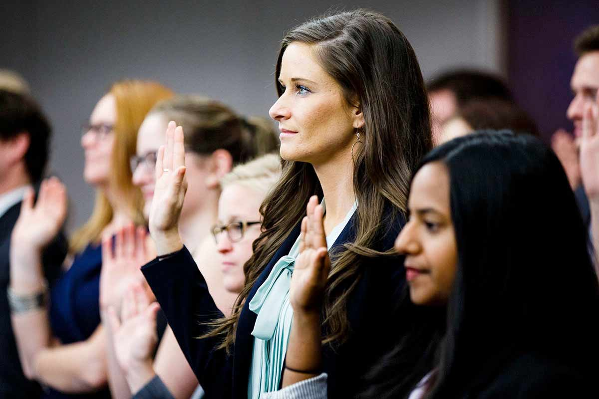 Law students raise their hands and take an oath during a swearing in ceremony.