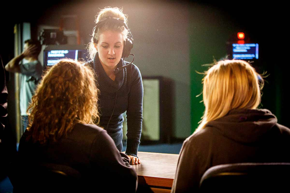 A student producer talks with talent during a production of a TommieMedia program.