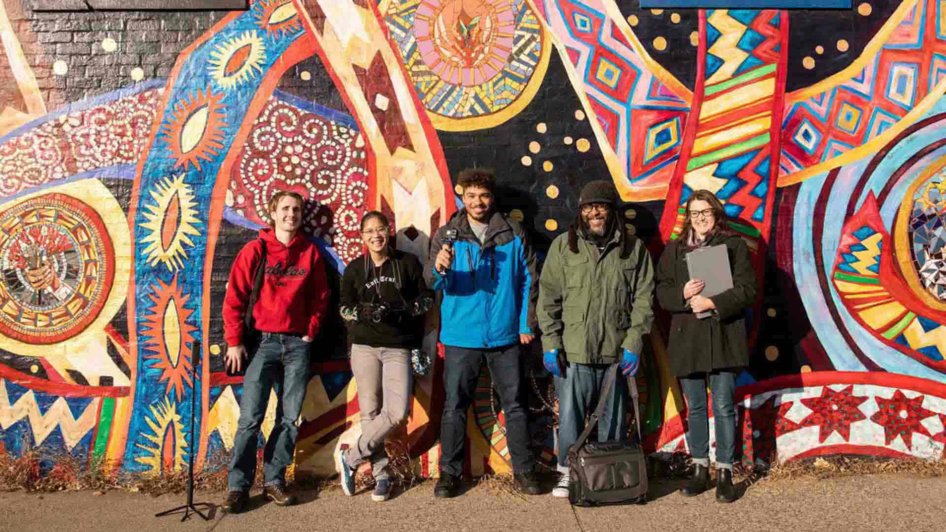 Student and faculty stand in front of a mural.