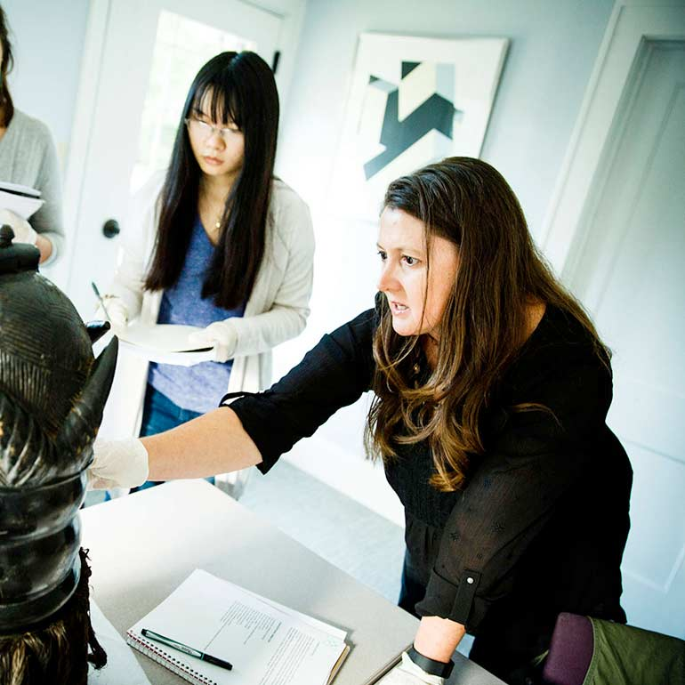 Professor Heather Shirey shows students how to examine a mask.