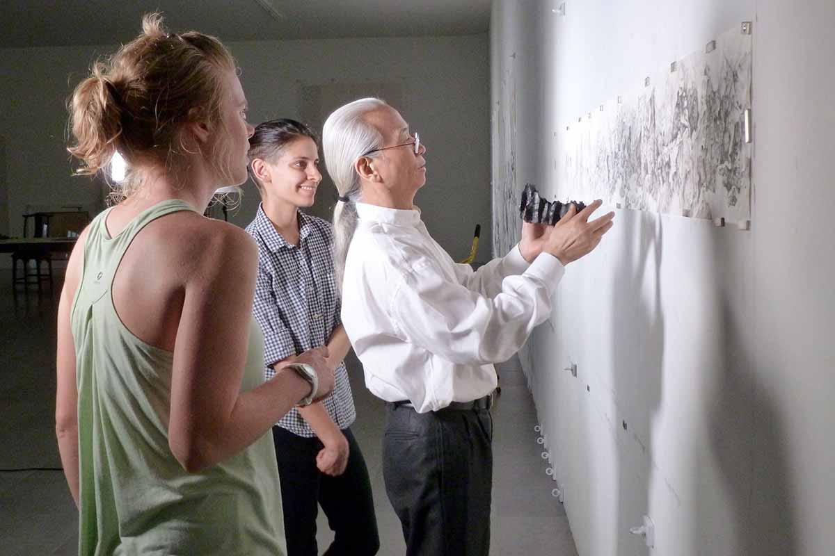 Three individuals analyze a piece of artwork displayed on a wall.
