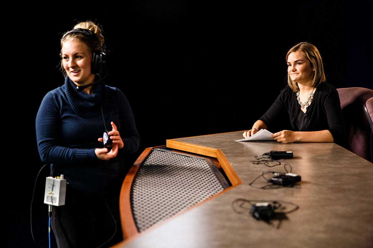 "A student producer and host are pictured on set during production of the TommieMedia program ""The Locker Room"" in the TV studio in O'Shaughnessy Educational Center (OEC)."