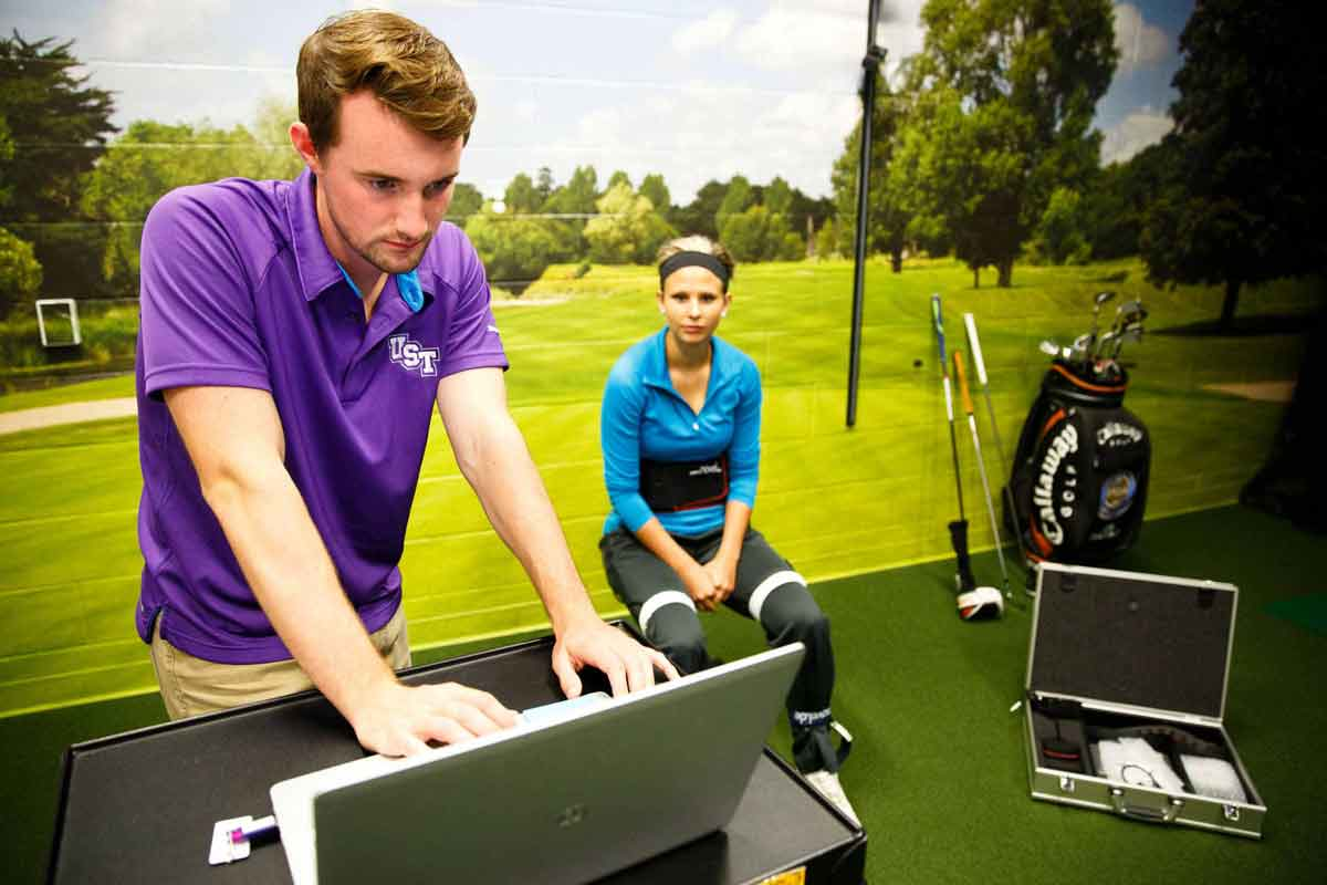 Student looks at a computer while another student watches in the Golf Simulation room