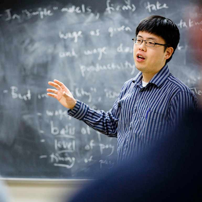 Professor Matthew Kim teaches an economics course.