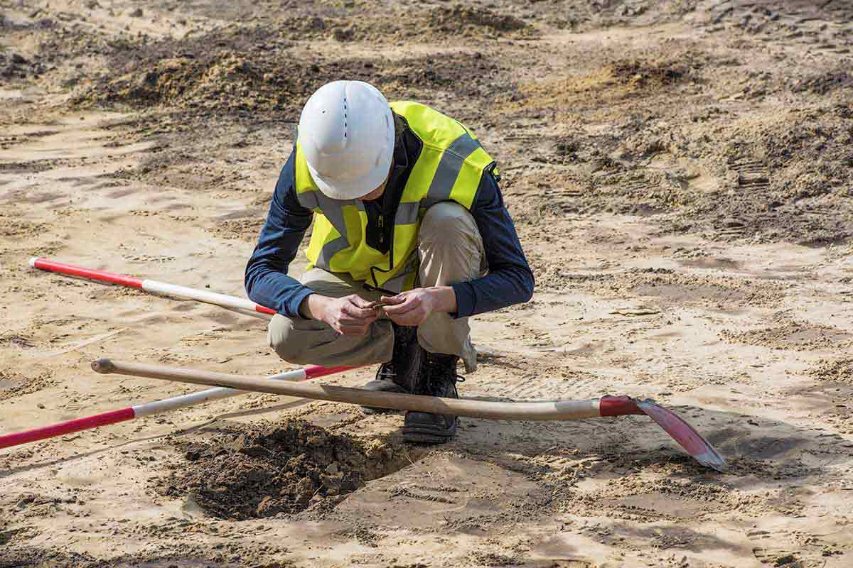Person in hardhat and hi-vis vest examines soil at a construction site.