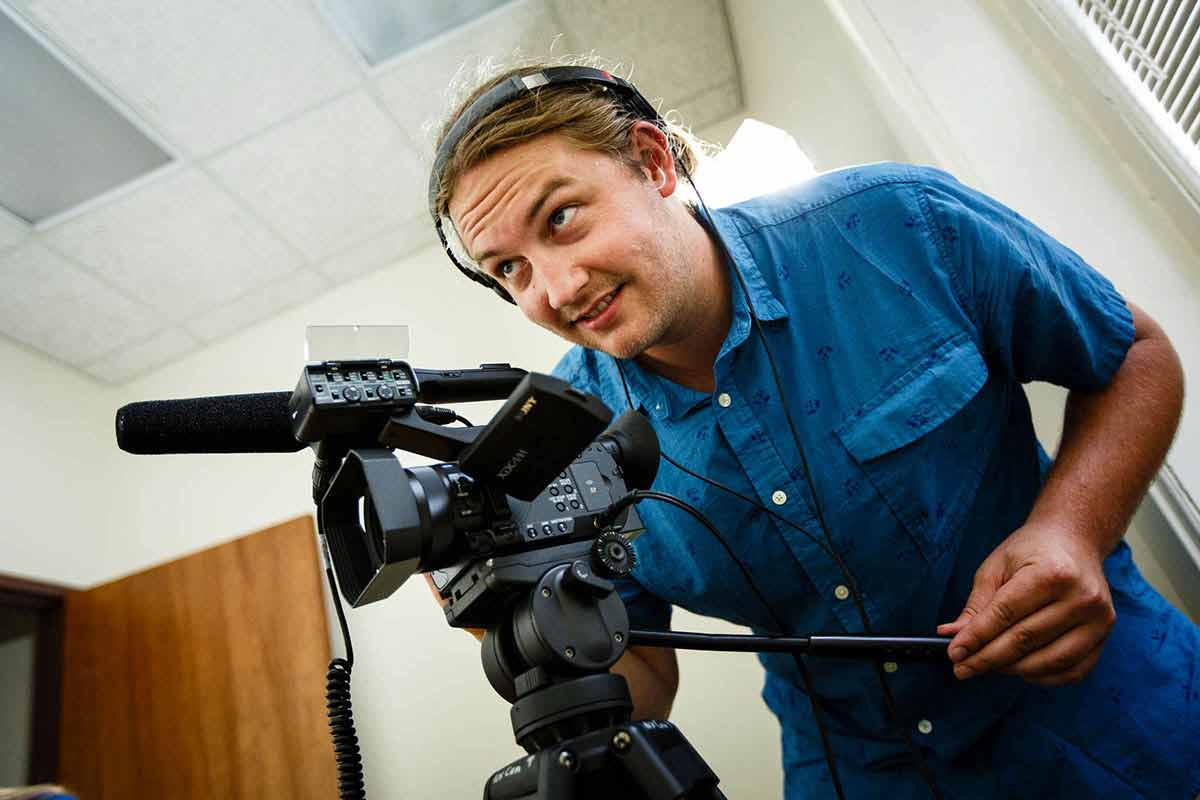 Zachary Neubauer operates a video camera during a staged film production.