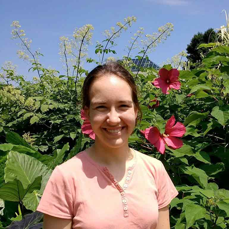 Photo of Erin Buchmann in front of flower bush.