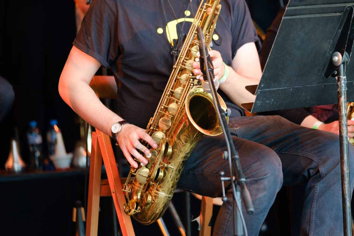 A close-up of a saxophone player performing on set.