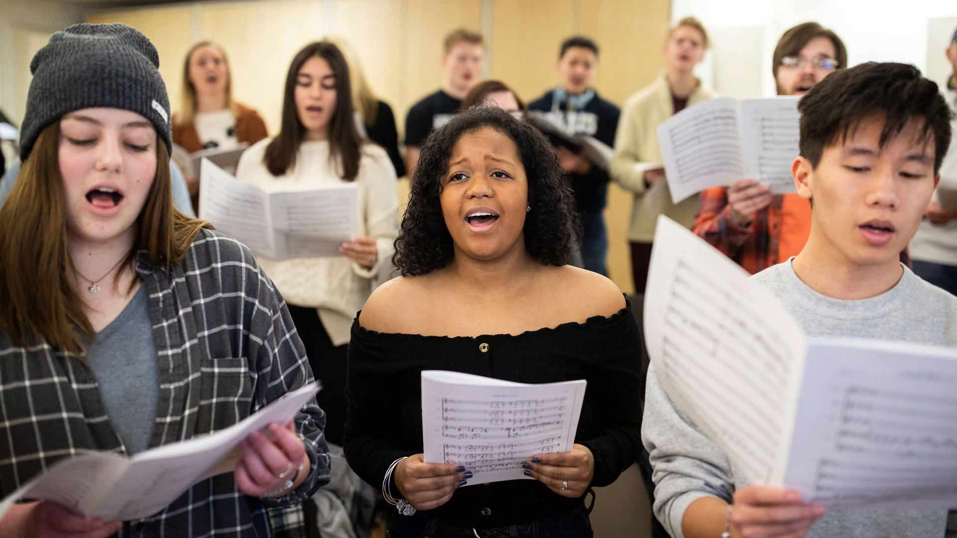 St. Thomas' Concert Choir ensemble rehearses with sheet music in hand.