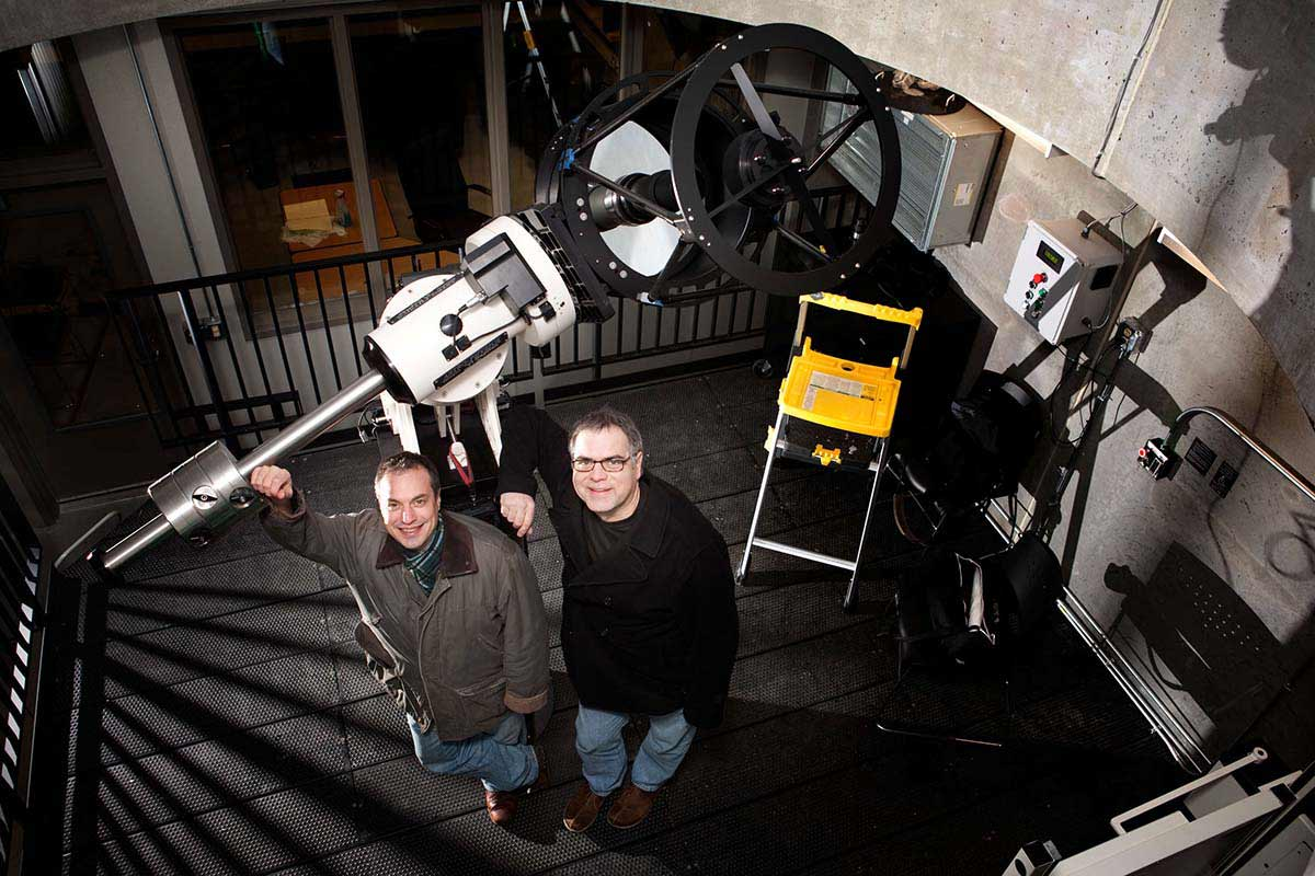 Physics professors Marty Johnston  and Gerry Ruch pose with the newly installed telescope