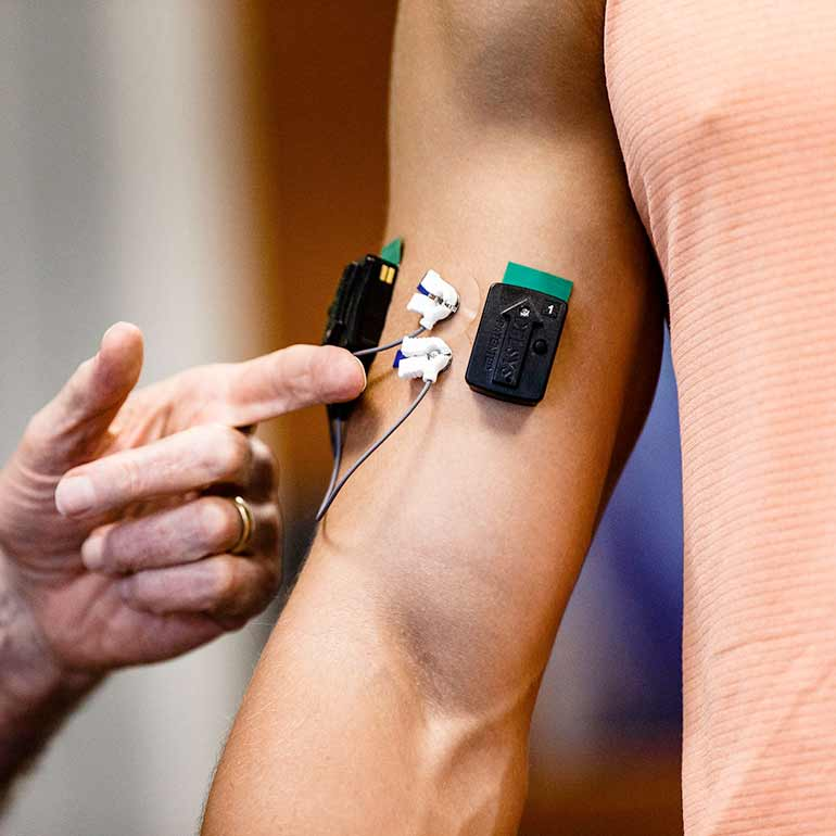 Sensors are attached to a student's bicep during a Health and Human Performance class.