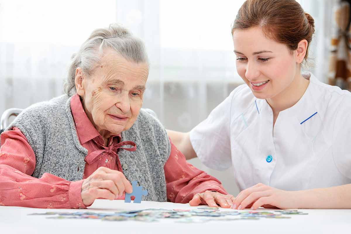 A nurse helping a senior citizen complete a puzzle.