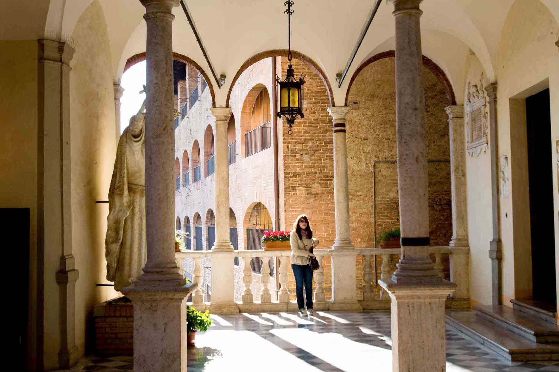 University employee is seen in a courtyard at the hour of Saint Catherine in Siena, Italy