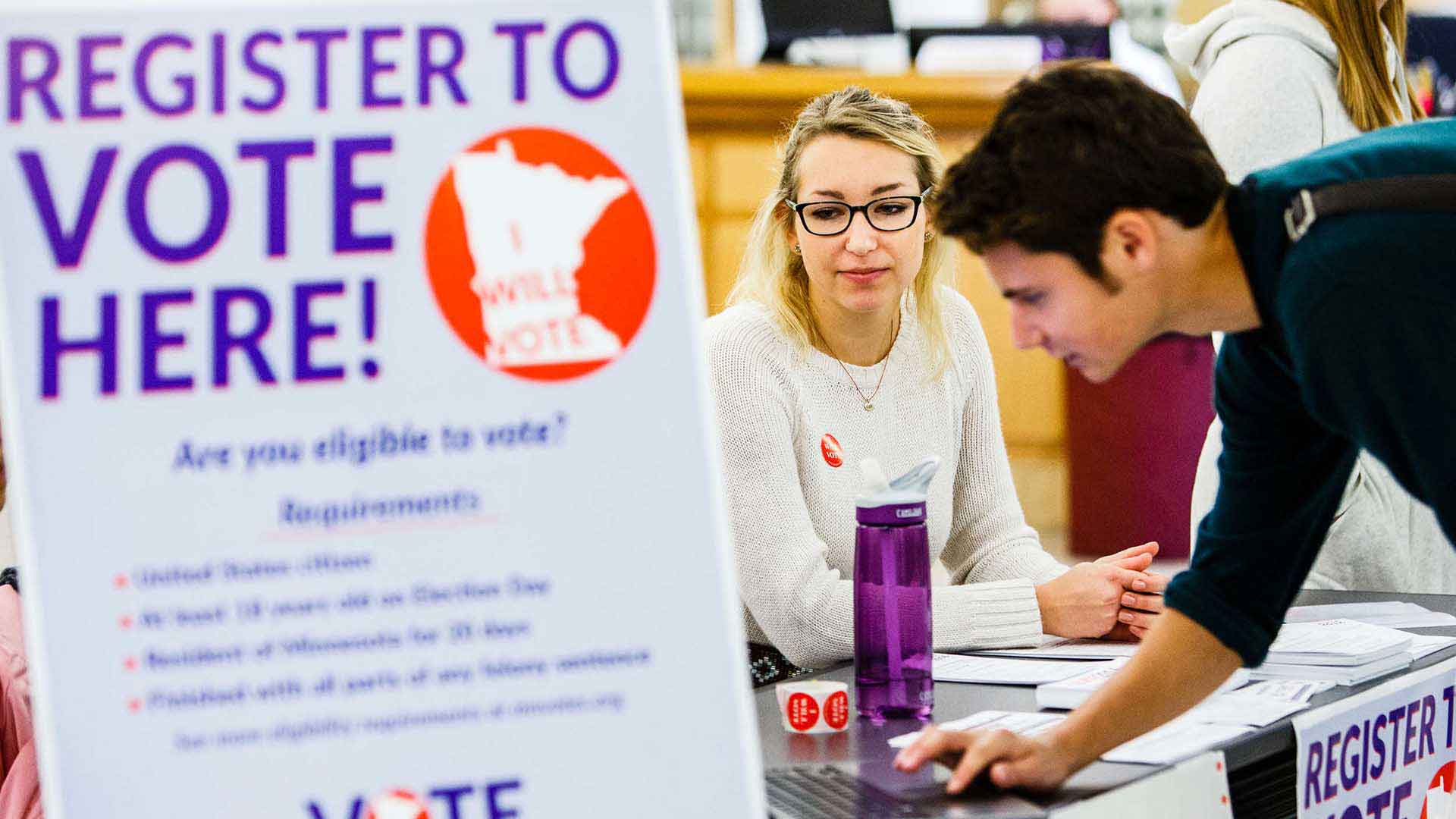 Hannah Ruskin helps a student register to vote during a voter registration drive by School of Social Work and Justice and Peace Studies students in the O'Shaughnessy-Frey Library Center.