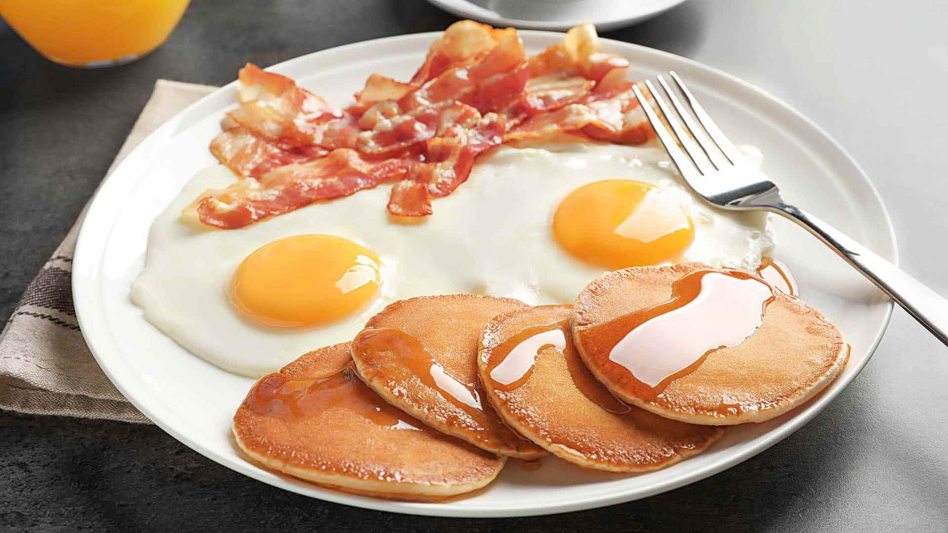 Plate of bacon eggs and pancakes