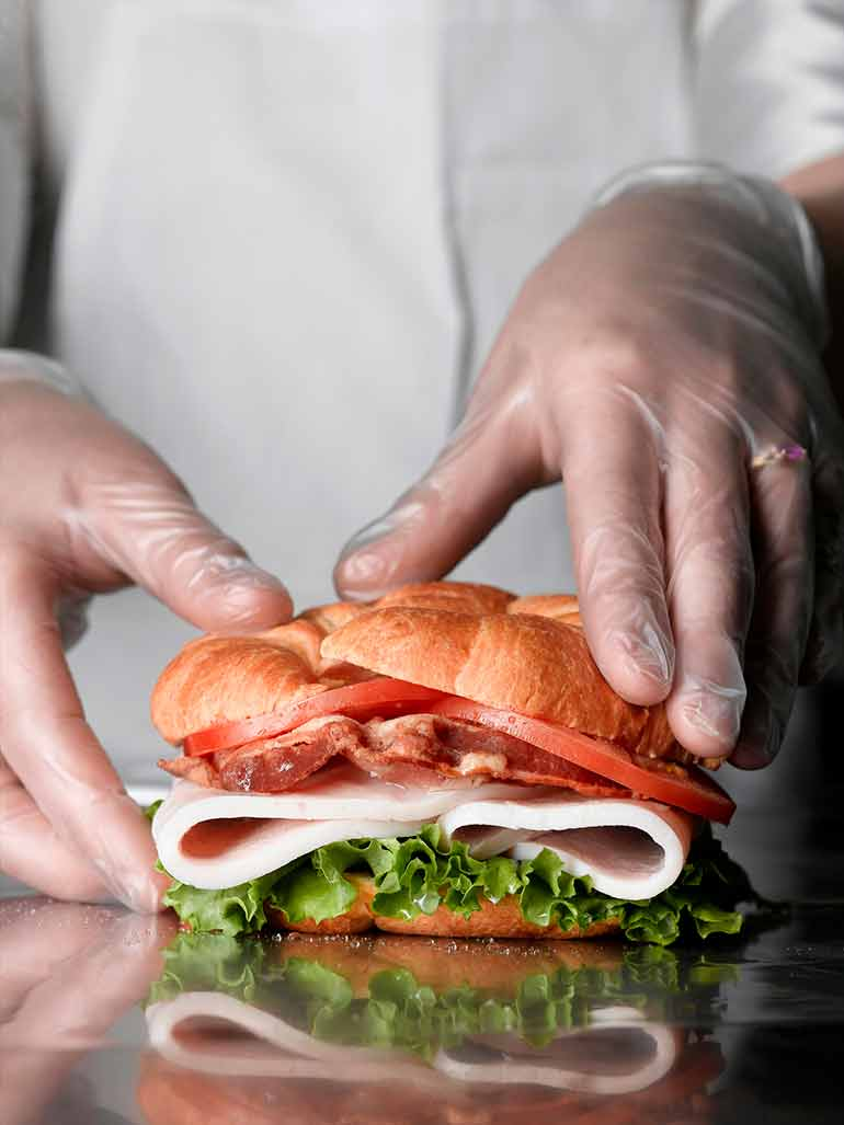 Sandwich being served by someone wearing gloves