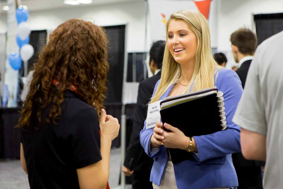 A student speaks with a recruiter at an employment event.
