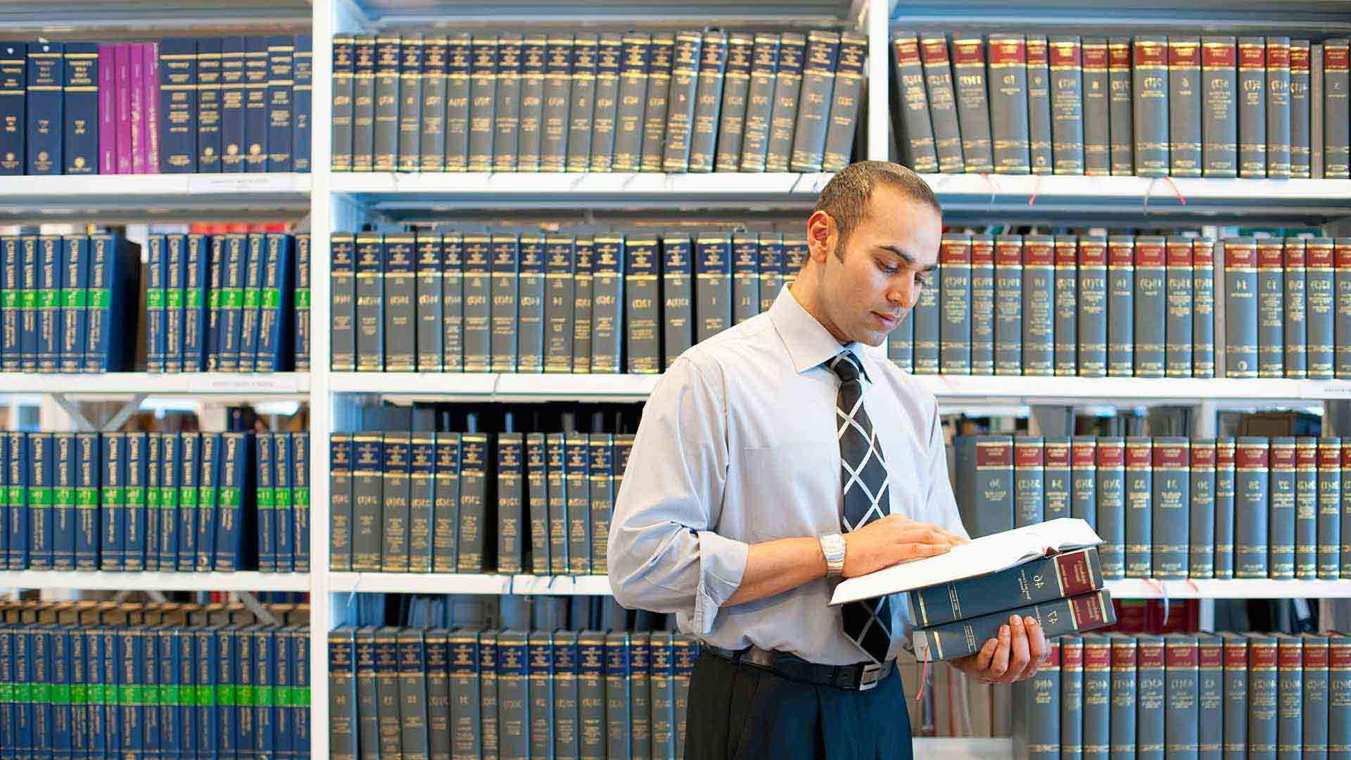 Man reading a book in a law library.