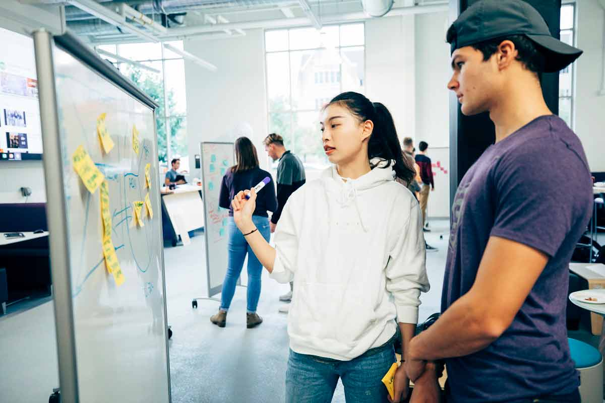Two students work on exercises on a whiteboard in the Innovation Space in the Facilities and Design Center.