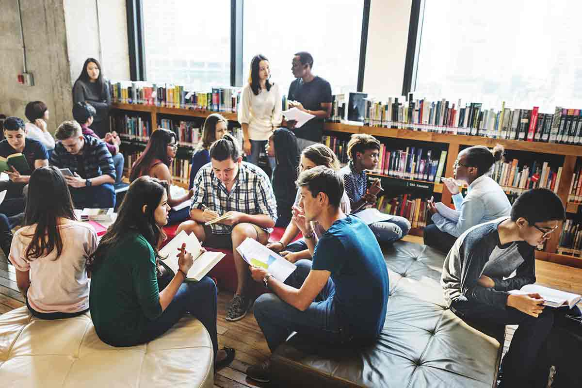 Students have small group discussions in a library.