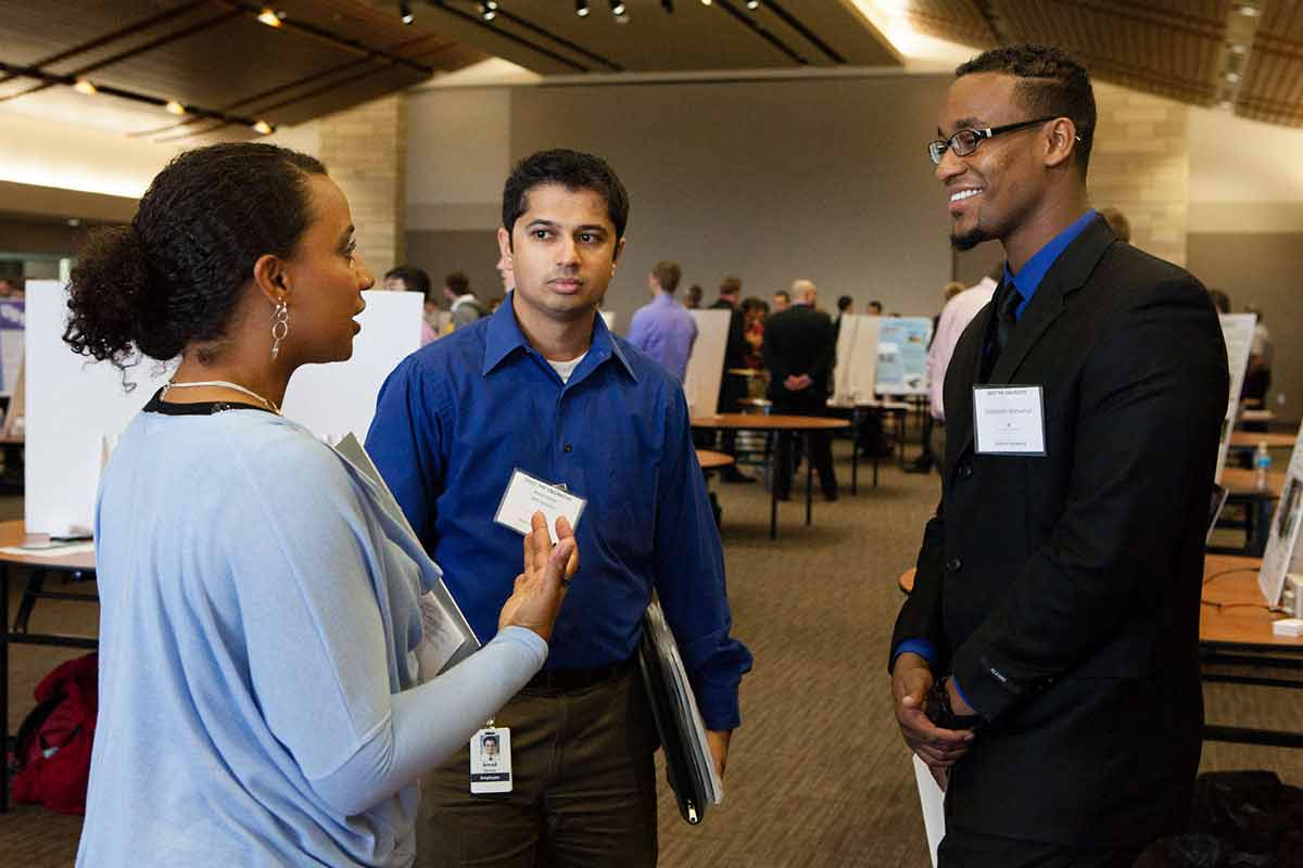 Students and potential employers converse during a career fair.