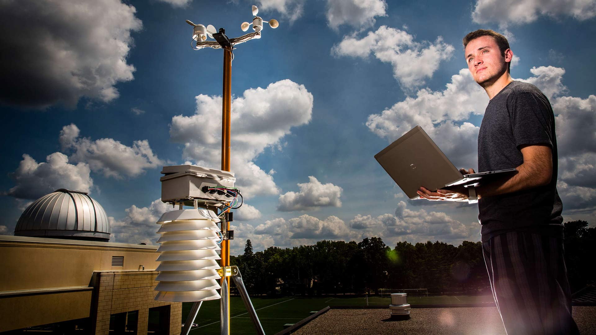 A engineering student stands next to the weather station project.