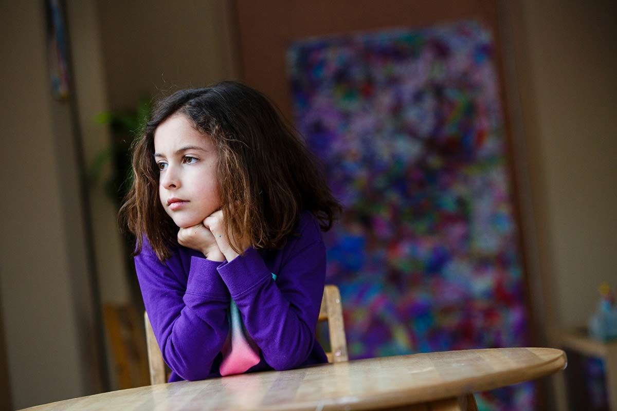 Young girl sits at table