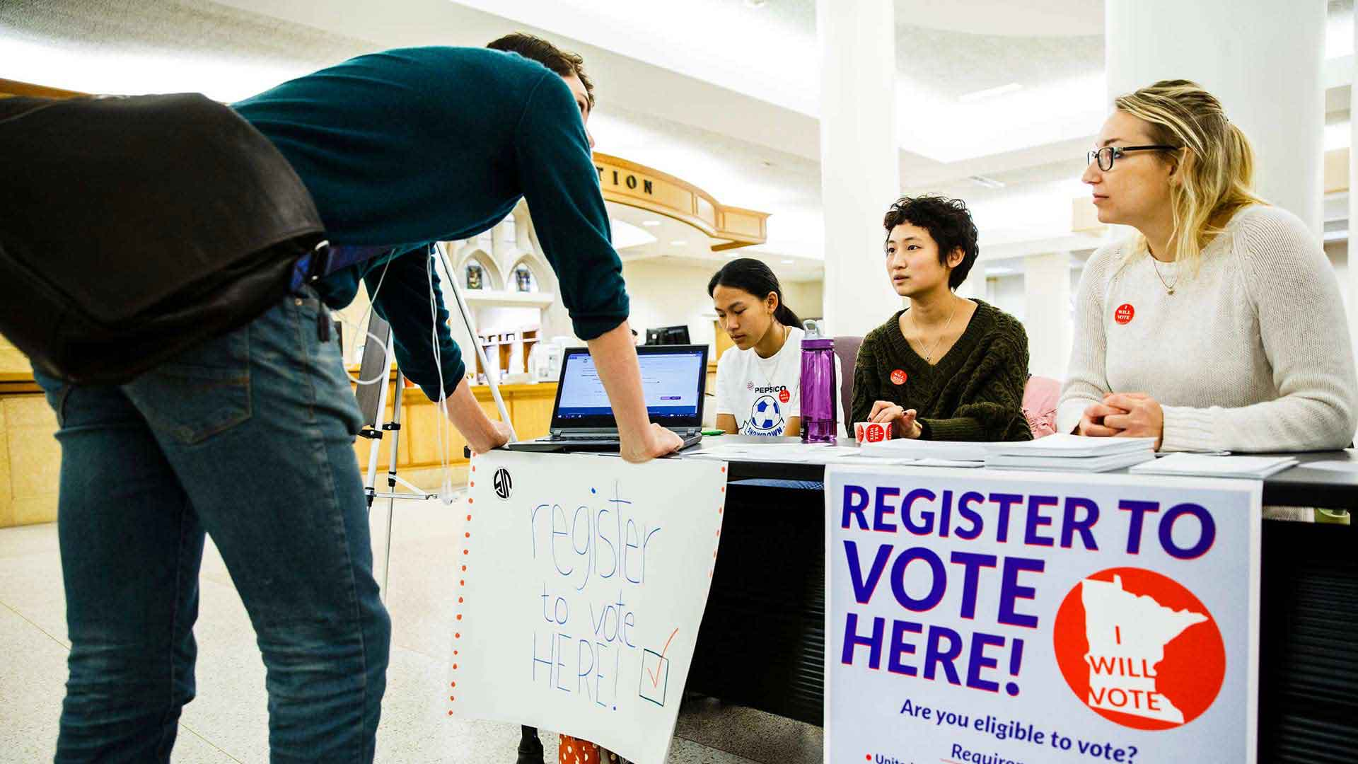 Students help a student register to vote