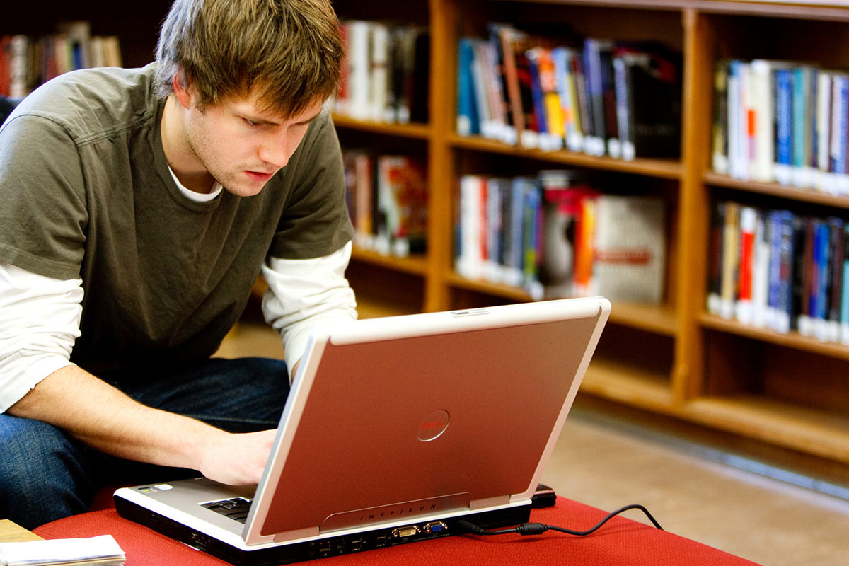 Student Zach Turman works on a laptop in O'Shaughnessy Frey Library.