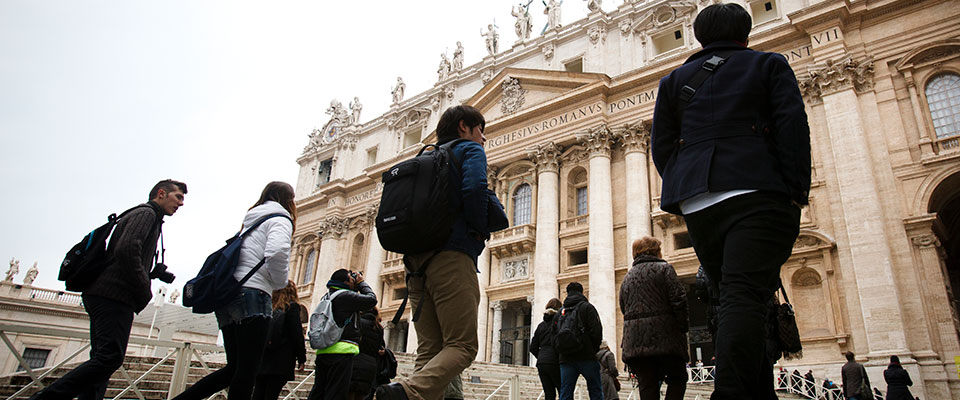 Students studying at the Bernadi Campus in Rome, Italy, walk across Saint Peter's Square with other tourists toward Saint Peter's Basilica for a tour on February 25, 2013.