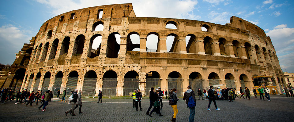 Tourists walk past the Coliseum in Rome, Italy, on February 26, 2013.