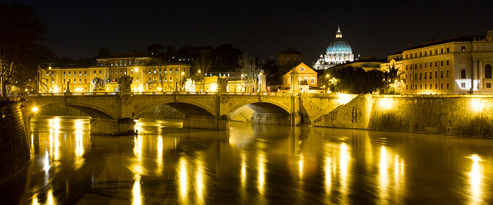 The dome of Saint Peter's Basilica is seen in the distance at night in this view from a bridge over the Tiber River on February 25, 2013.