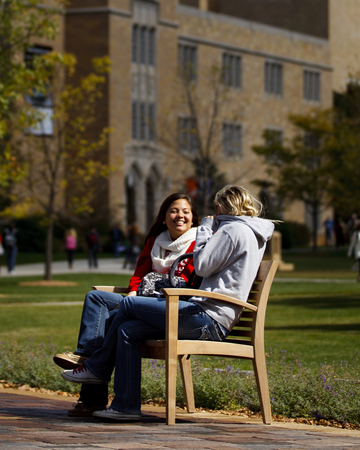 Two ladies laughing on a campus lawn bench.