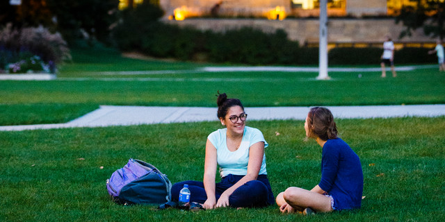 Two students sitting in the quad talking