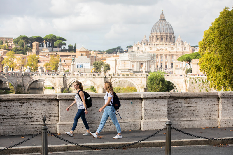 Two students with backpacks walking along a bridge in Rome. The dome of St. Peter's Basilica is in the background.