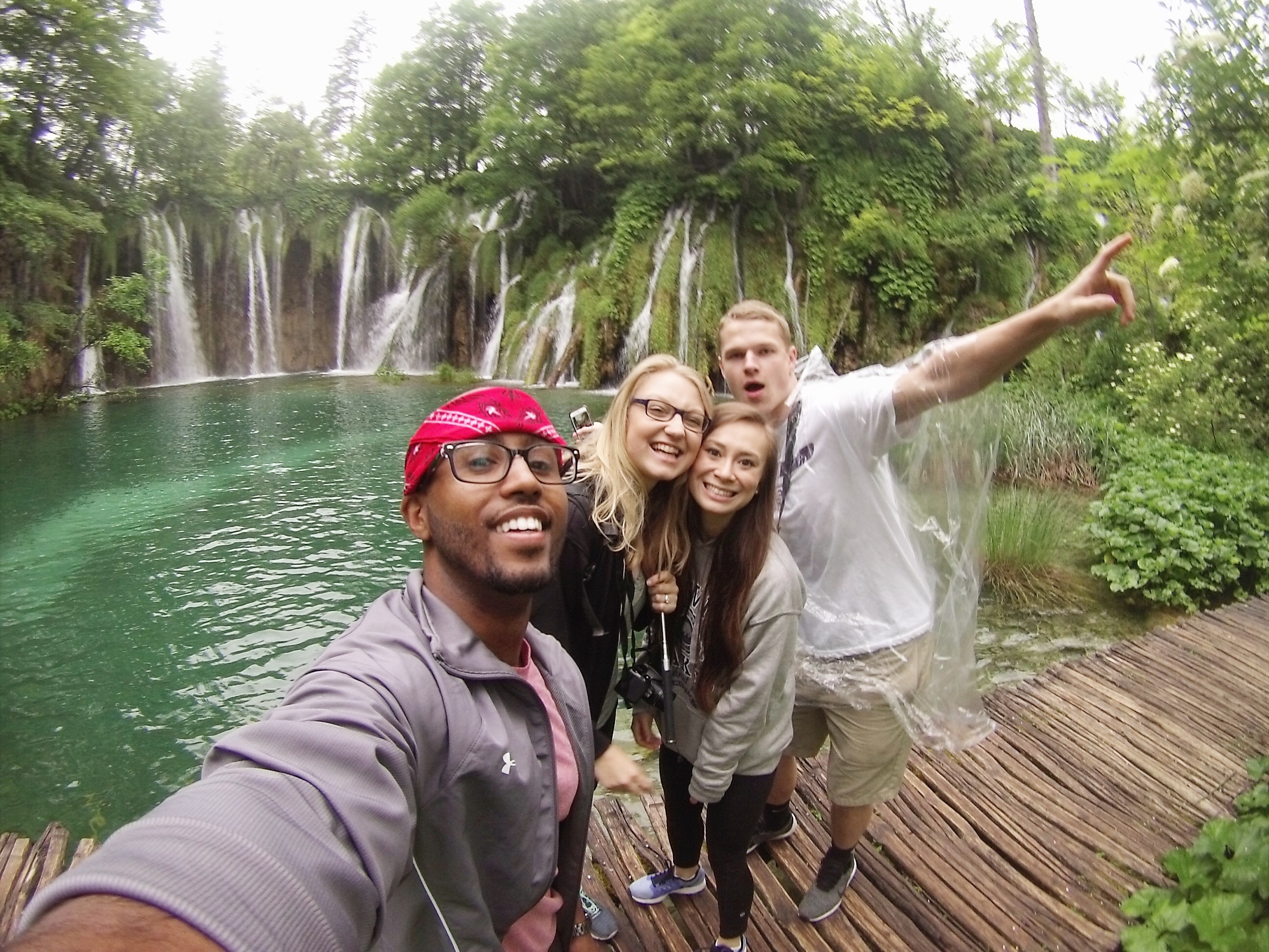 Four students taking a selfie in front of a waterfall